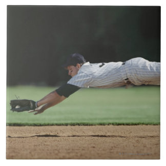 Baseball player in mid-air catching ball. large square tile