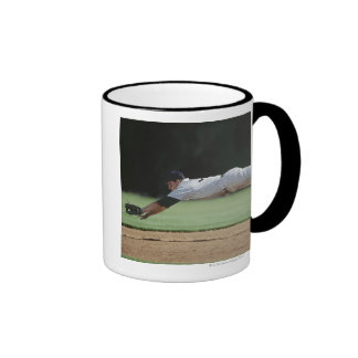Baseball player in mid-air catching ball. mugs