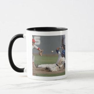 Baseball player sliding into third base with mug