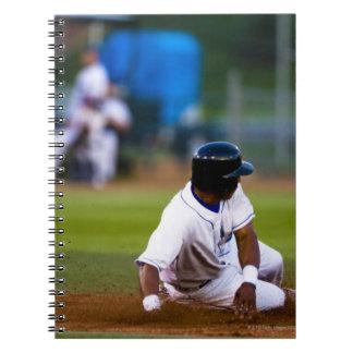 Baseball player sliding onto a base spiral notebook