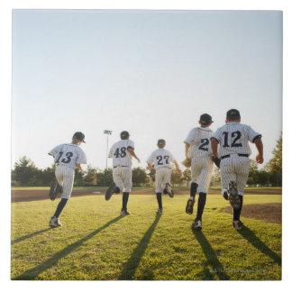 Baseball players (10-11) running on baseball tile