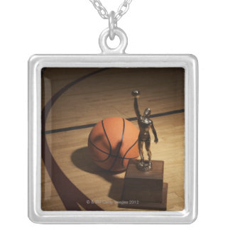 Basketball and trophy on basketball court, silver plated necklace