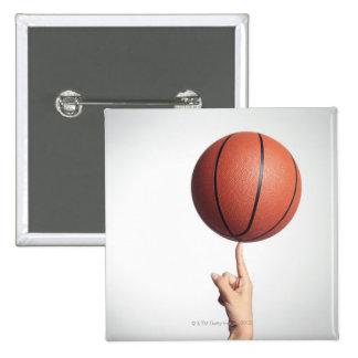 Basketball on index finger,hands close-up 15 cm square badge