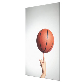 Basketball on index finger,hands close-up canvas print