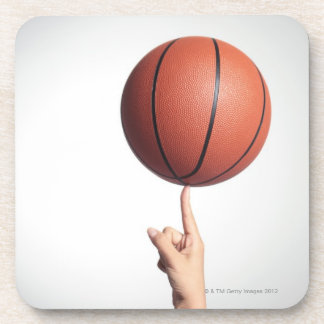Basketball on index finger,hands close-up coasters