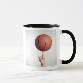 Basketball on index finger,hands close-up mug