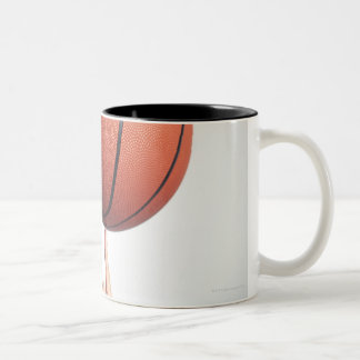 Basketball on index finger,hands close-up Two-Tone coffee mug