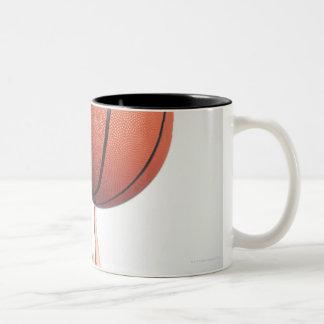 Basketball on index finger,hands close-up Two-Tone mug