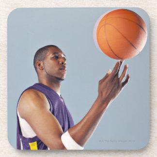 Basketball player balancing ball on one finger coaster
