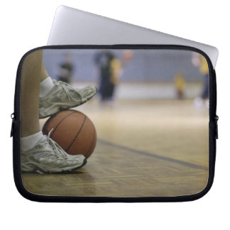 Basketball player holding ball with feet laptop sleeve