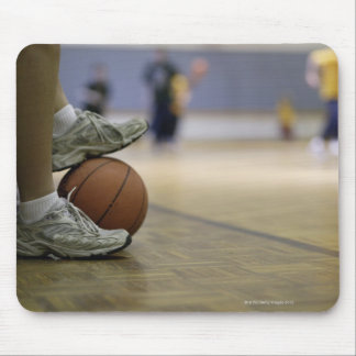 Basketball player holding ball with feet mouse mat