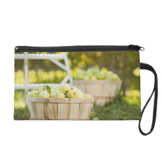 Baskets of apples in orchard wristlet clutches