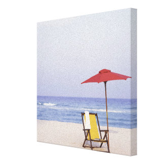 Beach Chair And Umbrella By Ocean Canvas Print