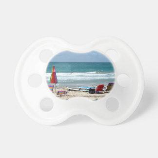 beach chairs surfboards umbrellas sand ocean pacifiers