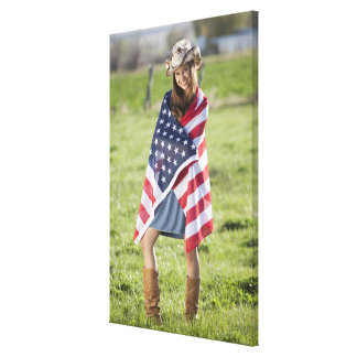 Beautiful cowgirl wrapped in American flag Canvas Print