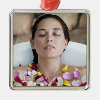 Beautiful young woman relaxing in bathtub with christmas ornament