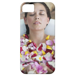 Beautiful young woman relaxing in bathtub with iPhone 5 covers