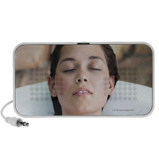 Beautiful young woman relaxing in bathtub with iPhone speakers