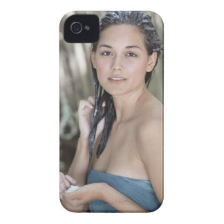 Beautiful young woman wrapped in towel and iPhone 4 cover
