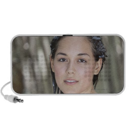 Beautiful young woman wrapped in towel and travelling speaker
