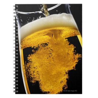 Beer been poured into glass spiral notebook