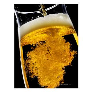 Beer been poured into glass, studio shot postcard