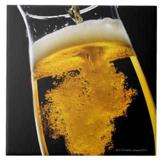 Beer been poured into glass, studio shot tile