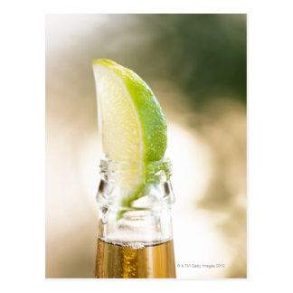 Beer bottle with lime wedge postcard