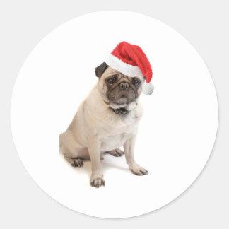 Beige pug with red santa hat on classic round sticker