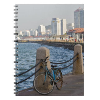 Bicycle at waterfront with Yantai city skyline, Spiral Notebook