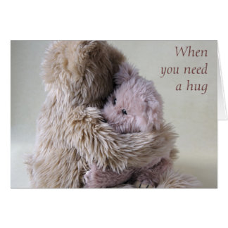 big teddy bear holds little bear card hug