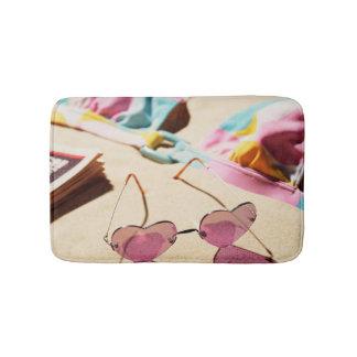 Bikini Top And Heart Shape Sunglasses On Beach Bath Mats