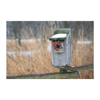 Bird, nest box with holiday wreath in winter canvas print