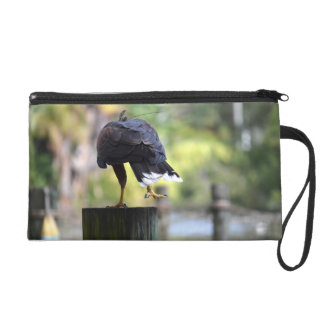 bird of prey back view on log foot up wristlet purses