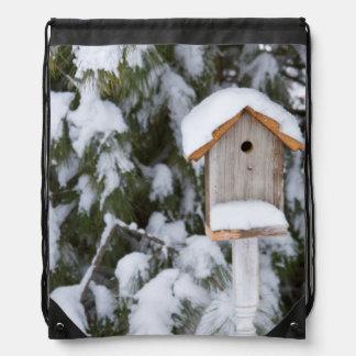 Birdhouse near pine tree in winter drawstring bag