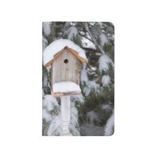Birdhouse near pine tree in winter journal