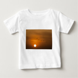 Birds flying in sunset baby T-Shirt