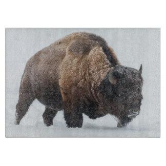 Bison walking in snow cutting board