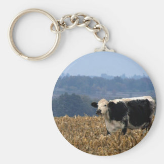 Black and White Cow grazes in freshly plowed field Basic Round Button Key Ring