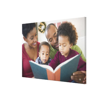 Black family reading book together stretched canvas print