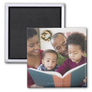 Black family reading book together square magnet