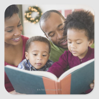 Black family reading book together square sticker
