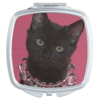 Black kitten wearing jeweled necklace compact mirror