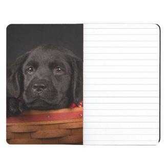 Black labrador retriever puppy in a basket journal