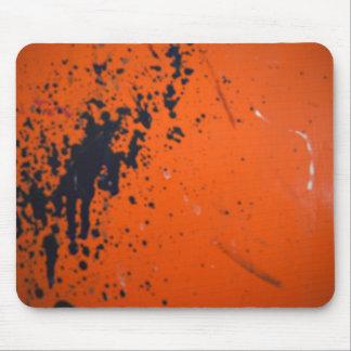 Black paint splatter on orange mouse mat