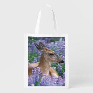 Black-tailed deer, doe resting in siky lupine, reusable grocery bag