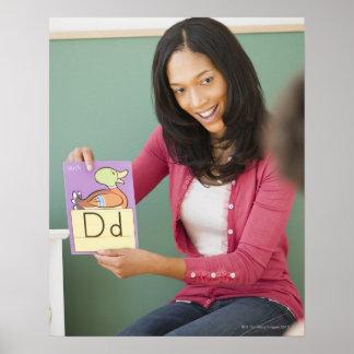 Black teacher showing letter d flash card to poster