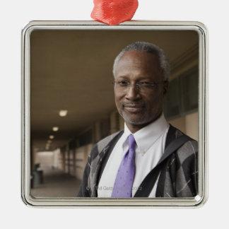 Black teacher standing in school corridor christmas ornament