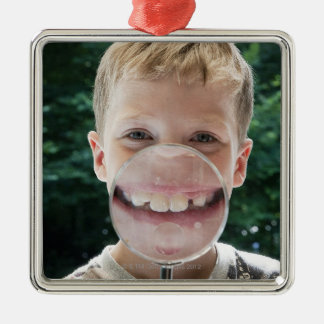 blond boy behind magnifying glass smiling christmas ornament
