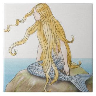 Blonde mermaid sitting on sea rock, side view. tile